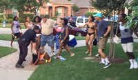 In an image from a video posted online, McKinney Cpl. Eric Casebolt is seen leaning on a girl he ordered to the ground.