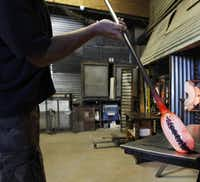 Glass blower Spencer Crouch dips the molten glass into small chunks of glass.