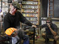 David Gappa, left, owner of Vetro Glass Blowing Studio in Grapevine, shapes a piece of glass as Spencer Crouch blows air into a blowpipe.