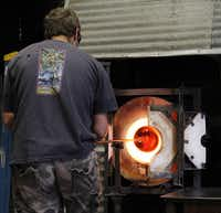 Glass blower Spencer Crouch places the molten glass into a furnace to heat at 2100 degrees so it can be shaped.