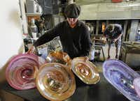 David Gappa, left, owner of Vetro Glass Blowing Studio in Grapevine, arranges his rondels as Spencer Crouch, a glass blower works.