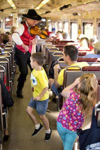 This photo provided by Grand Canyon Railway shows a performer playing violin onboard the railway train on its daily run between Williams, Arizona, and the Grand Canyon's South Rim. The railway has been running since 1901, carries 225,000 people a year, and offers history, sightseeing, scenery and entertainment.Guy Noffsinger  -  AP