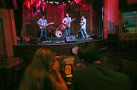 Troy Cartwright and his band Glen Wallace (left) on lead guitar, Ruben Salazar (right) on bass guitar, and Jeff Howe (background) on drums perform live original music onstage at Grover's in Frisco on Thursday, August 1, 2013.