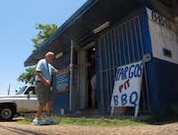Posse member Jim Rossman, right, holds the door for his dad Tom as they enter Fargo's Pit BBQ in Bryan, our second stop on the Gulf Coast BBQ Tour.