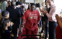 """Carol """"Mama"""" Hawkins, 58, walks the red carpet with other homeless people as volunteers cheer them  at the Omni Dallas Hotel on Monday."""