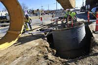 Construction workers work to install a manhole at the intersection of Malcolm X Boulevard and Elm Street in Deep Ellum.