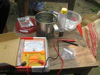 Pulak's home-based rapid arsenic water test, shown here in a Bangladesh village, includes a multimeter, test paper made out of tissue and business cards and nano magnet.Photo submitted by THABIT PULAK