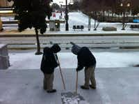 Carlos Lopez, right, and Derrick Forte, both building engineers at the Plaza of the Americas, break the ice that collected overnight across from the DART Pearl Station stop.