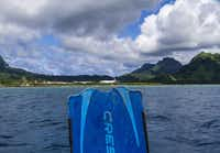 A jet sits on runway at Kosrae, Micronesia, taking off after passengers disembarked.  The view is from a dive boat with a diver who just arrived on that jet, getting ready for first dive on Kosrae.