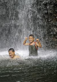 Young, native boys play in cascading spray of Sipyen Waterfall, Kosrae, Federated States of Micronesia (FSM).