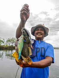 Local man holds string of fish he caught while snorkeling in Kosrae, Federated States of Micronesia (FSM).