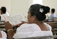 Micronesian women dressed in white lace sing four-part choral harmony during a church service in Lelu, Kosrae, Federated States of Micronesia. Congregational church services are virtually unchanged since original missionaries introduced Christianity in 1852.
