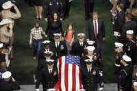 Taya Kyle and her children exit the stadium as the casket bearing her husband Chris Kyle's body is carried out during a memorial service for Chris Kyle at Cowboys Stadium in Arlington on February 11, 2013.