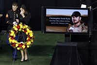 A member of the military consoles Taya Kyle after speaking at the memorial service for her husband Chris Kyle on Monday, February 11, 2013 at Cowboys Stadium in Arlington, Texas.