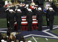 Military members salute during a memorial service for Chris Kyle at Cowboys Stadium in Arlington on February 11, 2013.