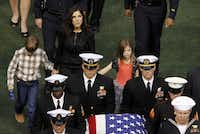 Taya Kyle and her children exit the stadium as the casket bearing Chris Kyle is carried out during a memorial service for Chris Kyle at Cowboys Stadium in Arlington on February 11, 2013.