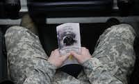 A person holds a program during a memorial service for Chris Kyle at Cowboys Stadium in Arlington on February 11, 2013.