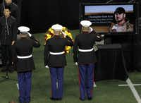 Members of the military salute after placing a wreath near the casket during a memorial service for Chris Kyle at Cowboys Stadium in Arlington on February 11, 2013.