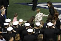 Taya Kyle far right, leads her two children to their seats at the beginning of  the memorial service for her husband Chris Kyle on Monday, February 11, 2013 at Cowboys Stadium in Arlington, Texas.