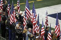People bow their heads during a prayer during the memorial service for former Navy SEAL Chris Kyle on Monday, February 11, 2013 at Cowboys Stadium in Arlington, Texas.