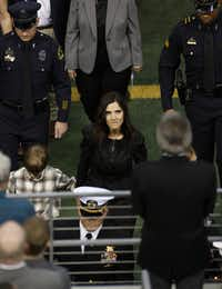 Taya Kyle, center, wife of former Navy SEAL Chris Kyle walks behind the honor guard carrying her husband's coffin during the memorial service on Monday, February 11, 2013 at Cowboys Stadium in Arlington, Texas.