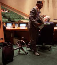 Al Lipscomb returns to collect his belongings after overturning his chair and walking out of a discussion on redistricting during a May 1991 Dallas City Council meeting.