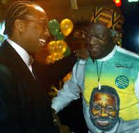 Dallas County Commissioner John Wiley Price (left) is congratulated by Al Lipscomb during a party at Billy G's Rhythm & Jazz Club in Dallas  celebrating Price's re-election in March 2004.