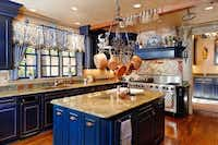 The spacious kitchen has royal blue cabinets.Steve Reed