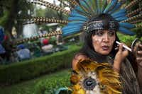Street performer  Judit Pozos puts the finishing touches on her Aztec costume. She performs blessings with incense and a conch shell.Rebecca Blackwell  -  AP