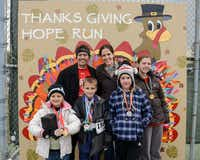 """The Morphis family stands in front of the """"thankful wall"""" at the inaugural Thanks Giving Hope 5K and Fun Run on Nov. 28. Participants wrote grateful messages on feathers that were pinned to the turkey depicted on the wall.Photo submitted by ANGELA LOWRY PHOTOGRAPHY"""