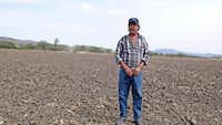 Leodegarco Ramirez Ramirez stands in his cornfields where his family has toiled for generations. Now his sons and nephews work for manufacturing plants.