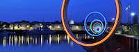 In Nantes, France, on the Isle of Nantes, an art installation of 18 rings along Quai des Antilles glows in red, green and blue hues at nightfall, with each ring framing different angles of the waterfront cityscape.