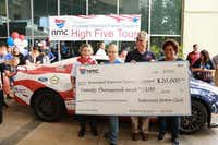 Hughlene Stokes (from left), Heidi Vincent, Col. John Folsom and Donna Smith receives a check at the High Five Tour stop at National Motor Club in Irving.Photo submitted by NATIONAL MOTOR CLUB
