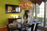 Soft green walls blend with dark woods in the Hollmullers' dining room combining traditional and contemporary accents.
