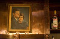 A portrait of John F. Kennedy and his wife, Jacqueline, hangs behind the bar at the Kennedy Room, a small tavern in the Montaigne Club in Uptown.