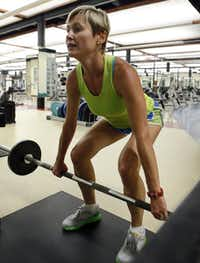 Gina Garcia, the assistant fitness director at SMU, dead lifts during a work out at SMU's Dedman Center.