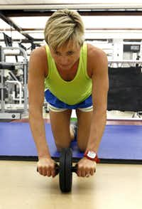 Gina Garcia, the assistant fitness director at SMU, uses a rolling Ab Wheel during a work out at SMU's Dedman Center,