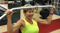 Gina Garcia, assistant fitness director at SMU, works out with a pull-down cable.