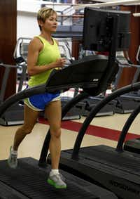 Gina Garcia, the assistant fitness director at SMU, starts her work out with a 15 minute warm up on the treadmill at SMU's Dedman Center.Ron Heflin