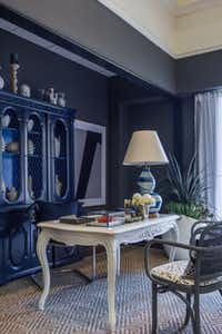 A traditional hutch donated to Dwell with Dignity by One King's Lane was infused with new life via blue-lacquer paint. Gray paint also revitalized a petite pair of cane-back chairs.
