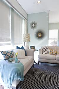 The living room's pale couches are dressed with lively pillows and a soft blue throw.