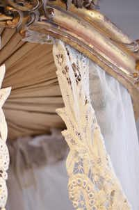 A piece of repurposed European lace is attached to an antique carved bed crown. Installed over a desk or table in a bedroom, the soft style creates a creative, dramatic letter-writing table or reading nook like no other.
