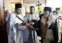 Father Vasile Tudora (left) presented His Eminence Metropolitan Isaiah with ceremonial scissors during the Thyranixia on Saturday.