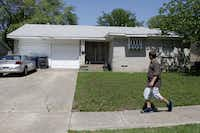 Thomas Savage, who lives in the neighborhood, walks past  the home of Aaron Ramsey and Elizabeth Ramsey  on Clearwater in northeast Dallas.