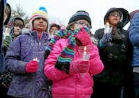 One of  Arnav Dhawan's classmates, Chloe Town, 10, (middle), attended Wednesday's candlelight vigil  with others outside the family's Frisco home. The Collin County Medical Examiner has not ruled on the cause of Arnav's death pending toxicology results.
