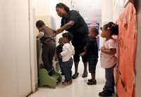 Preschool teacher Deleatrice Smith helps children drink from the water fountain. In addition to providing child care, the center has hosted health and literacy festivals and community holiday dinners.