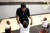 Petrella Booker, executive director of Dallas Bethlehem Center, received an enthusiastic greeting from Nikolas Gainey, 4, in the gym this week as Isaiah Campbell-Ivy (left), 3, and Kamron Jackson, 4, rolled by. The center serves about 500 children with an annual budget near $550,000.