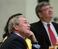 Former President George W. Bush watches a presentation on the 360-degree video screen in Freedom Hall during a formal handoff ceremony at the Bush Center.