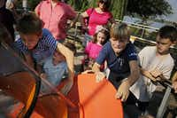 (From left) Jason Fowler, Jake Newell, David Burke and Henry Kern work an Archimedean screw in the Pure Energy section of the Rory Meyers Children's Adventure Garden Friday, September 6, 2013 in Dallas.