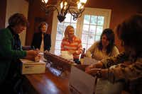 "(From left) MaryBeth Shapiro, Betsy Kennard, Laurie Bret, Angela Schmidt and Ginny Leone pack boxes with goods during a ""boxing club"" get-together Tuesday, April 23, 2013 in Dallas. The group of five mothers, who call themselves the ""Boxing Moms,"" have gathered regularly for the last three years to make care packages for their children in college."
